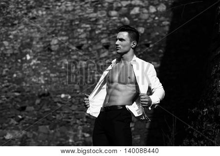 Man half face bare-chested young handsome sensual model in shirt gaped open poses outside black and white on masonry background
