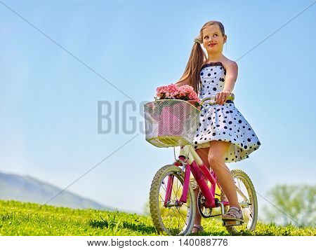 Nice girl ride on bicycle . Child girl wearing white polka dots dress rides bicycle with pink flowers basket. Green grass and blu sky on summer park background.
