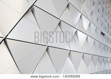Abstract photo close-up view of modern aluminum ventilated facade of triangles