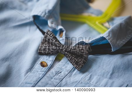 Close-up of blue shirt with a bow tie on a hanger. Black bow tie with scientific symbols. Clothes. Special occasion suit. Clothes on a hanger.