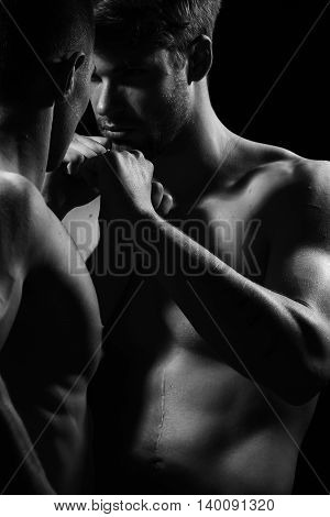 Young men boxing with sexy muscular body and bare torso in studio black and white