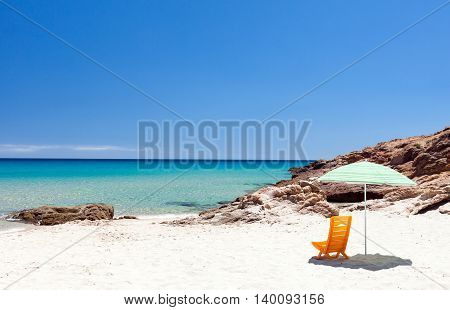 Lonely lounge chair with sun umbrella on a beach in Sardinia Italy