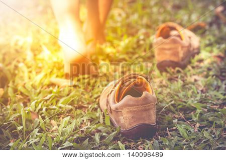 Child take off leather shoes. Close up child's foot learns to walk on grass reflexology massage. Kid relax in garden with sunlight. Shallow depth of field (dof) selective focus. Retro style.