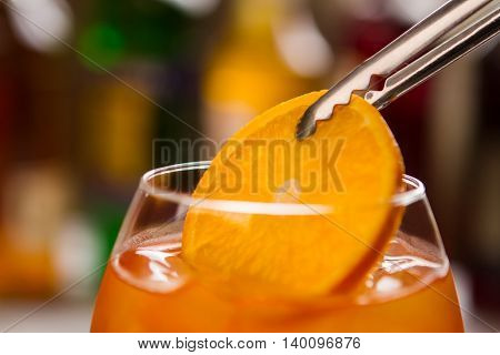 Tongs hold orange slice. Drink of bright color. Aperol spritz with quality wine. Enjoy your beverage.