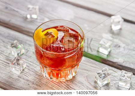 Glass with dark orange beverage. Lemon rind and ice. Negroni with bitter and vermouth. Simple recipe of alcoholic cocktail.
