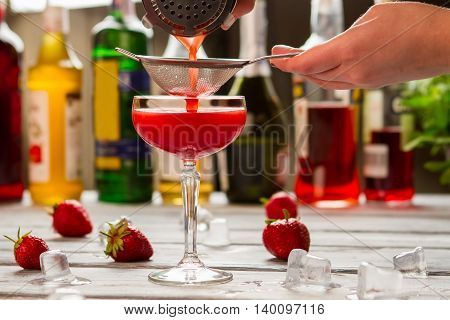 Red beverage pours through sieve. Male hand holding a sieve. Bartender's recipe of clover club. Fresh summer drink.