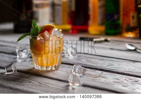 Glass with orange drink. Grapefruit slice and mint. Exotic beverage served at club. Cobas cocktail with citrus fruit.