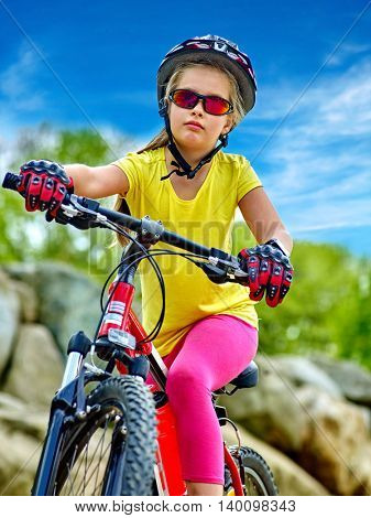 Bikes bicyclist girl. Girl rides bicycle into mountains over rocks. Girl wearing helmet and gloves on bicycle in mountaineering aganist blue sky . Mountaineering is good for health.