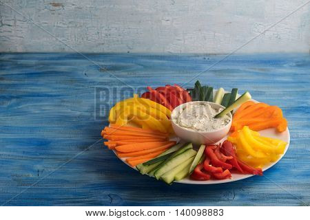 Colorful vegetable sticks in a plate with dip sauce on blue table