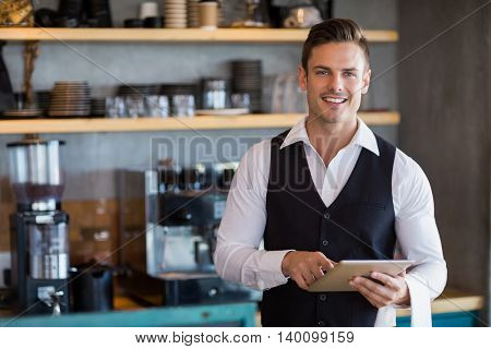 Portrait of waiter holding digital tablet in restaurant