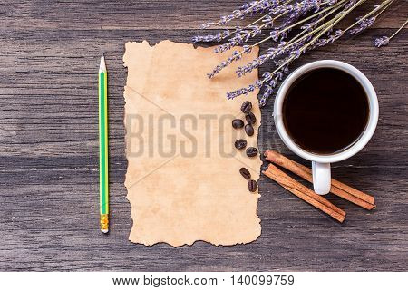 Old paperpencil and coffee with lavender flower on dark wooden table background. top view with copy space
