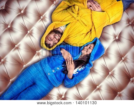 Smiling woman in blue pijamas and man in yellow bathrobe have a rest on the bed