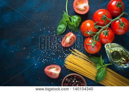 Ingredients for cooking Italian pasta - spaghetti tomatoes basil and oil. Top view with copyspace. Organic food.