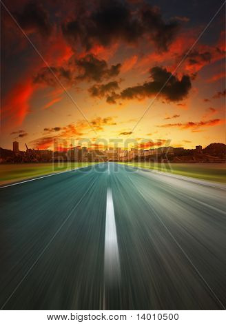 Asphalt road to city under dramatic sunset