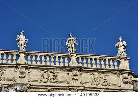 Monumental baroque balustrade of Palazzo Maffei (17th century) with greek gods statues of Mercury Apollo and Minerva in Piazza delle Erbe square in the center of Verona