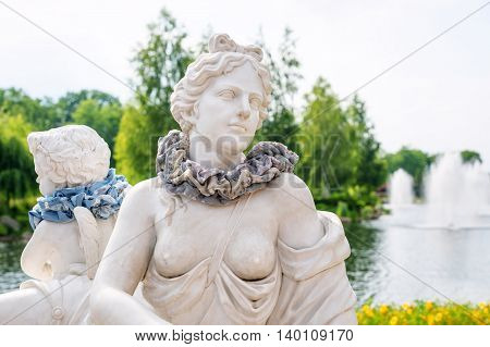 Marble statue of greek goddess with naked breast and scarf on her neck. Fashion and clothing concept