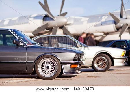 Right front side of two old european sport cars with plane on background.