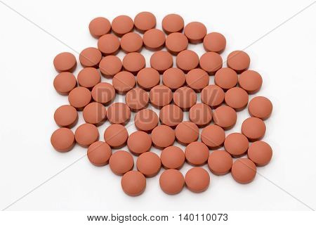 Spilled pile of red tablets ibuprofen on white background