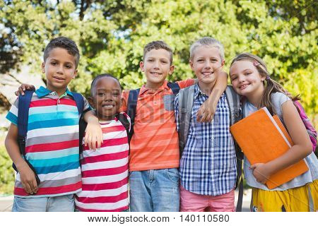 Portrait of smiling schoolkids standing with arms around in campus at school