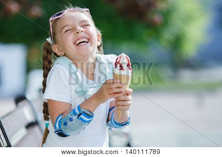 A cute little girl with two long braids, wearing sun glasses in a pink frame with glass in the shape of hearts, wearing gold earrings, wearing a white blouse and blue shorts holding an ice cream in waffle cone sitting on a bench in the park after rollerbl