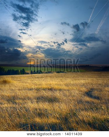 Sunset on dry field with dark blue storm clouds
