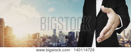 Businessman extending hand with panoramic cityscape of Bangkok city in sunrise, vintage tone