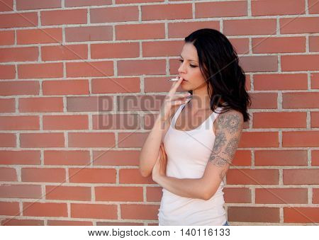 Rebel brunette woman with tight shirt smoking a cigarette on background of red bricks
