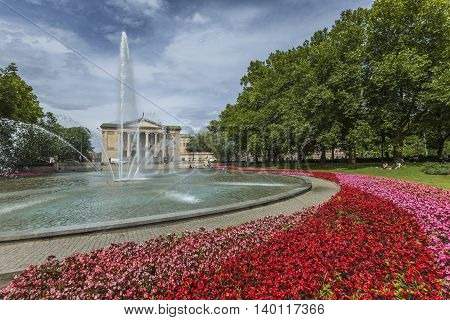 Poznan, Poland - July 09, 2016: The Grand Theatre (opera), Green Park And Fountain,red Flowers Aroun