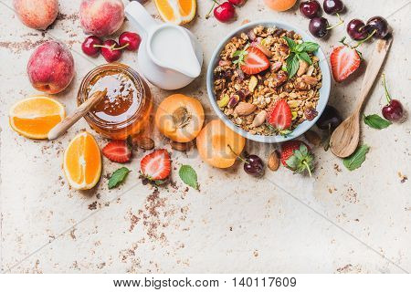 Healthy breakfast ingredients. Oat granola in bowl with nuts, strawberry and mint leaves, milk in pitcher, honey in glass jar, fresh fruits, berries and mint on light concrete background, top view, copy space, horizontal composition