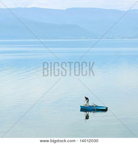 Alone fisherman on huge lake in little boat