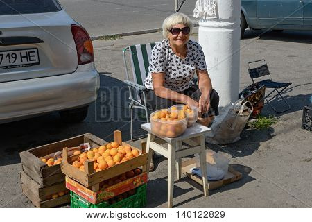 Aged Woman Is Selling Apricots On City Sidewalk.