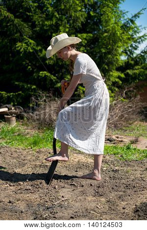 girl in a cowboy hat with a shovel digging a big hole