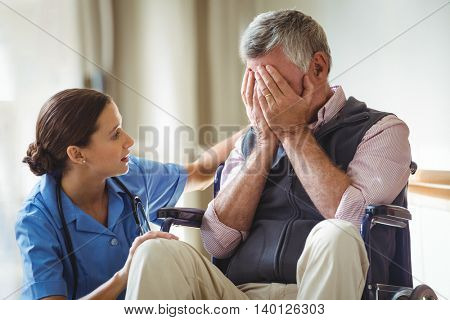 Nurse taking care of sad senior man in a retirement home
