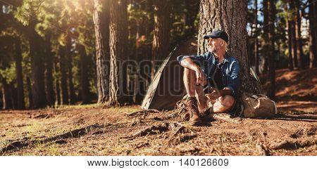 Mature Man Sitting At A Campsite