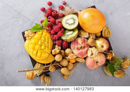 Fresh and ripe tropical fruit board including mango, longan, kiwi and granadilla