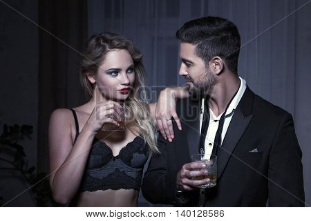 Macho man in night club with blonde woman and drink