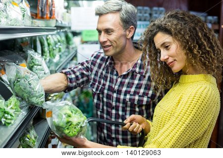 Happy couple selecting vegetables in organic section of supermarket