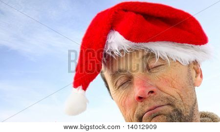 Drunk man in santa's hat over sky background