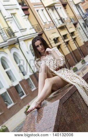 Girl in a long dress sitting on the parapet of the street. Boho style. Outdoors.