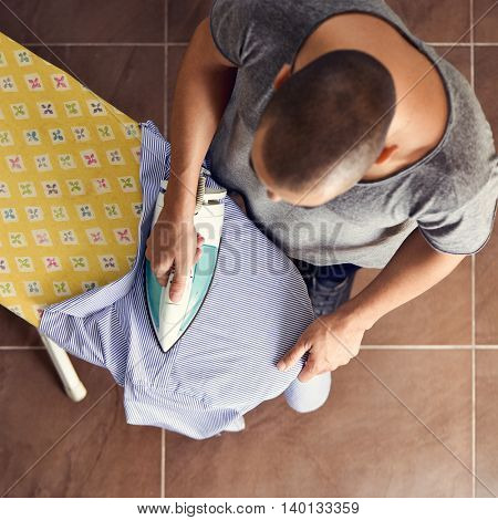 high-angle shot of a young man ironing a striped shirt with an electric iron on an ironing board
