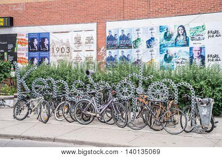Toronto Canada - 2 July 2016: Bike racks and Kensington neighbourhood metal sign in Toronto Canada.