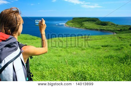 Young woman with backpack taking photo of a nature