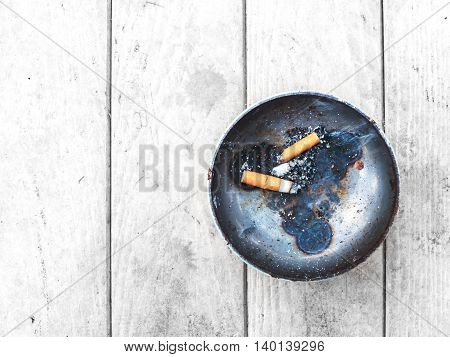 cigarette and metal ashtray on dirty wooden table top view.