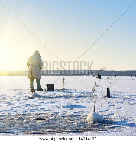 Fisherman on ice. Focus on front bunch in snow hill