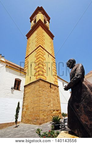 View of a church with a tall bell tower (Iglesia de Nuestra Senora del los remedios) with a statue in the foreground Estepona Malaga Province Andalucia Spain Western Europe.