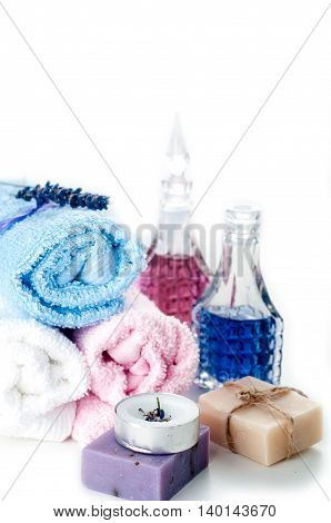 Lavender essential oil colorful stones and towel on a white background