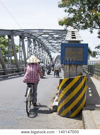 Hue, Vietnam - Jun 17, 2016: Asian woman with conical hat cycling ahead Truong Tien bridge over Huong river. Truong Tien bridge is one of the symbol of Hue ancient capital.