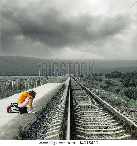 Joven espera tren en la estación