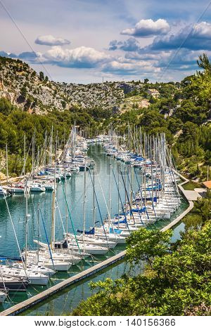 Picturesque small bay - Calanques with turquoise water. White sailboats moored in rows near the shore. Calanque National Park - small fjords between Marseille and Cassis
