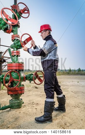 Oilfield worker repairing well head valve wearing red helmet and work clothes with the radio in his pocket. Oil and gas concept.
